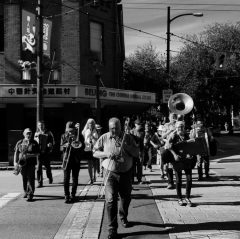 Musicians crossing a street playing instruments