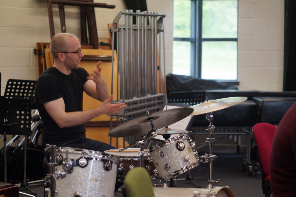 a photograph of James Wood gesturing behind a drum kit