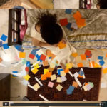 Decorative colour image of a figure on a bed with pieces of coloured paper surrounding them as seen from above.