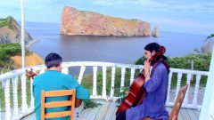 a photo of Reza and Fili performing in the Gaspe on a balcony overlooking the sea.