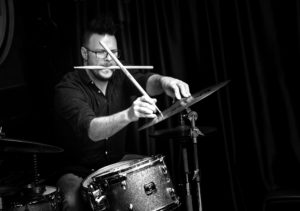 Photo of a mon with a drum stick in his mouth playing a cymbal with a stick in his hand.